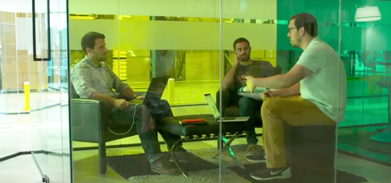 Three men meeting in a small meeting space with glass walls
