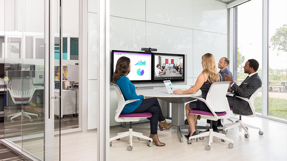 People in a huddle room web conferencing